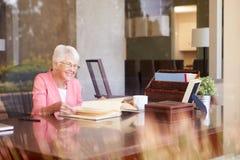 Ältere Frau, die Foto-Album durch Fenster betrachtet Stockfotografie