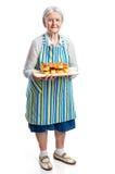 Ältere Frau, die frische Brötchen hält stockfotos
