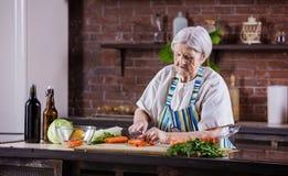 Ältere Frau, die Frischgemüse für Salat hackt lizenzfreie stockfotografie