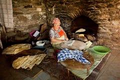 Ältere Frau, die Gebäck für traditionelles Lebensmittel Gozleme innerhalb der rustikalen Küche des alten türkischen Dorfs macht Stockfotos
