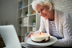 Ältere Frau, die Geburtstag über Laptop feiert stockfotos