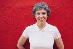 Ältere Frau, die gegen roten Hintergrund steht Lizenzfreie Stockfotos