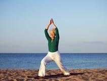 Ältere Frau, die gegen Strandhintergrund ausdehnt lizenzfreies stockfoto