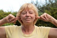 Ältere Frau, die Geräusche blockiert Lizenzfreie Stockfotos