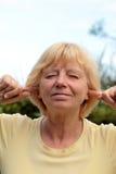 Ältere Frau, die Geräusche 2 blockiert Lizenzfreies Stockfoto