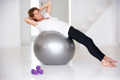 Ältere Frau, die Gymnastikkugel verwendet Stockbild