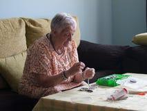 Ältere Frau, die Halsketten macht Stockfoto