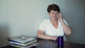 Ältere Frau, die am Handy spricht stock footage