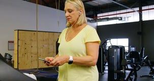 Ältere Frau, die Handy während der Übung 4k verwendet stock video