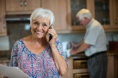 Ältere Frau, die am Handy während Mann arbeitet in der Küche spricht Stockfotos