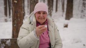 Ältere Frau, die heißen Tee beim Sitzen auf einer Bank im schneebedeckten Park trinkt Großmutter nach Weg im neuen ai stock footage