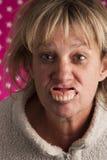 Ältere Frau, die heraus Zähne spuckt Stockbild