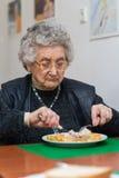 Ältere Frau, die ihr Mittagessen isst Stockbild