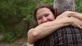 Ältere Frau, die ihre Ehemannnahaufnahme im Park umarmt stock footage