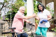 Ältere Frau, die ihrem Ehemann eine Flasche Wasser nach dem Radfahren gibt Lizenzfreie Stockfotos
