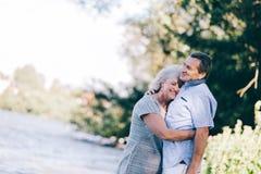 Ältere Frau, die ihren Ehemann umarmt Lizenzfreie Stockbilder