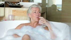 Ältere Frau, die im Bad trinkt Champagne sich entspannt stock footage