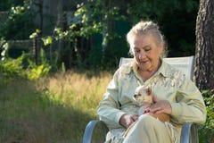 Ältere Frau, die im Garten mit kleinen Chihuahua sitzt stockbilder