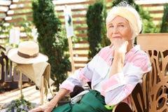 Ältere Frau, die im Garten stillsteht lizenzfreies stockfoto