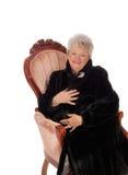 Ältere Frau, die im Lehnsessel sitzt Stockfotos