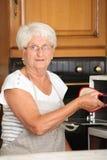 Ältere Frau, die im Ofen kocht lizenzfreies stockfoto
