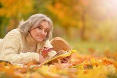 Ältere Frau, die im Park stillsteht Lizenzfreies Stockfoto
