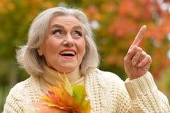 Ältere Frau, die im Park stillsteht Lizenzfreie Stockfotografie