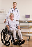 Ältere Frau, die im Rollstuhl mit Doktor sitzt Stockbild