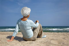 Ältere Frau, die im Sand auf dem Strandmeer sitzt Stockbild