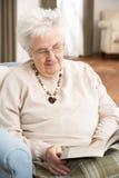 Ältere Frau, die im Stuhl sich entspannt Stockfoto
