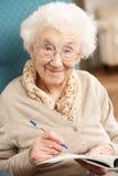 Ältere Frau, die im Stuhl sich entspannt Stockfotografie