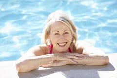 Ältere Frau, die im Swimmingpool sich entspannt Lizenzfreies Stockbild