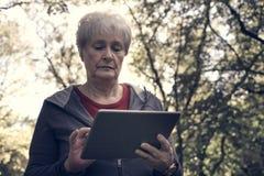 Ältere Frau, die im Wald steht und auf iPod schreibt clo stockbilder