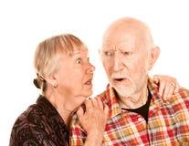 Ältere Frau, die Informationen mit skeptischem Mann teilt Stockfotografie