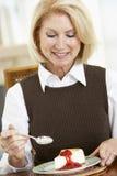 Ältere Frau, die Käsekuchen isst stockfotografie
