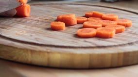 Ältere Frau, die Karotten auf einem hackenden Brett schneidet stock footage
