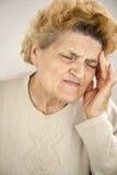 Ältere Frau, die Kopfschmerzen hat Stockfoto