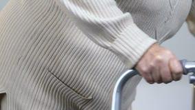 Ältere Frau, die langsam mit Rahmen, leidende Schmerz in den Gelenken, Pflegeheim geht stock footage