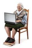 Ältere Frau, die Laptop-Computer ower Weiß verwendet Stockbilder