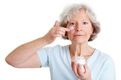 Ältere Frau, die Lotion anwendet Stockbild