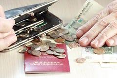 Ältere Frau, die Münzen in ihren Händen zählt Stockfotografie