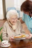 Ältere Frau, die Mahlzeit gedient wird lizenzfreie stockbilder