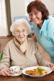 Ältere Frau, die Mahlzeit von Carer gedient wird Lizenzfreies Stockfoto