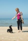 Ältere Frau, die mit Dachshund am Strand spielt Lizenzfreies Stockfoto