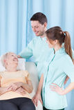 Ältere Frau, die mit Doktoren spricht stockbild