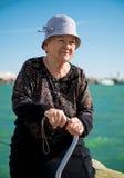 Ältere Frau, die mit einem Stock sitzt Stockbild