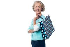 Ältere Frau, die mit Einkaufstasche aufwirft Lizenzfreies Stockbild