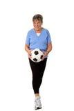 Ältere Frau, die mit Fußball geht Stockfotografie