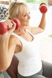 Ältere Frau, die mit Gewichten arbeitet Lizenzfreie Stockfotos