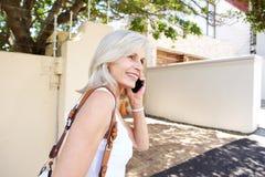 Ältere Frau, die mit Handy auf Bürgersteig geht und spricht Stockfotos